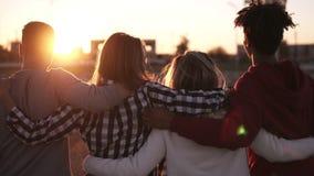 Gruppo di amici che camminano che abbraccia insieme e che si diverte nella città Sono due ragazze e due ragazzi nei loro anni ven archivi video