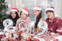 Gruppo di amici che celebrano il Natale a casa e che mostrano 2019 fotografie stock libere da diritti