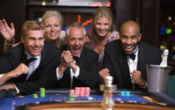 Gruppo di amici che celebrano vittoria alla tabella delle roulette Fotografie Stock