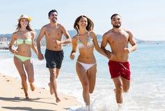 Gruppo di amici che corrono sulla sabbia alla spiaggia Fotografia Stock Libera da Diritti