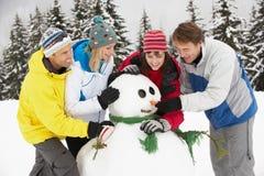 Gruppo di amici che costruiscono pupazzo di neve sulla festa del pattino Fotografie Stock Libere da Diritti