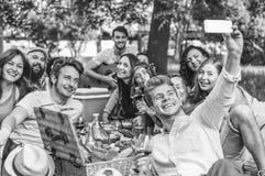 Gruppo di amici che fanno un barbecue di picnic e che prendono selfie con lo smartphone mobile in parco all'aperto fotografia stock libera da diritti