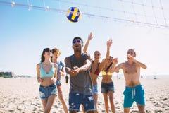 Gruppo di amici che giocano al pallavolo della spiaggia alla spiaggia Immagini Stock Libere da Diritti