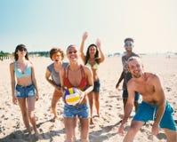 Gruppo di amici che giocano al pallavolo della spiaggia alla spiaggia Fotografia Stock