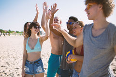 Gruppo di amici che giocano al pallavolo della spiaggia alla spiaggia Fotografie Stock