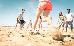 Gruppo di amici che giocano a calcio sulla spiaggia Fotografie Stock Libere da Diritti
