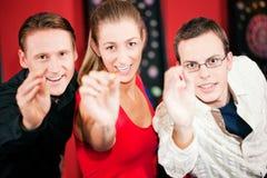 Gruppo di amici che giocano i dardi Immagini Stock Libere da Diritti