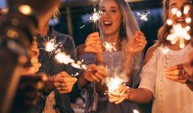 Gruppo di amici che godono con le stelle filante nella sera Fotografia Stock Libera da Diritti