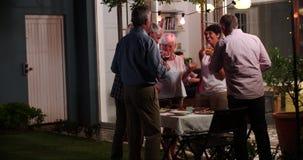 Gruppo di amici che godono del partito all'aperto delle bevande di sera archivi video