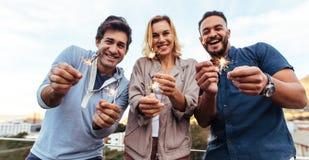 Gruppo di amici che godono del partito del tetto con le stelle filante Fotografie Stock Libere da Diritti