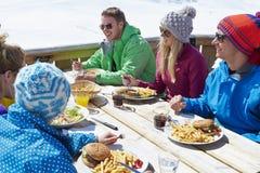 Gruppo di amici che godono del pasto in caffè a Ski Resort immagini stock