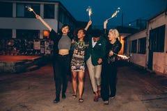 Gruppo di amici che godono fuori con le stelle filante Fotografie Stock Libere da Diritti