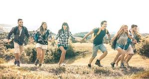 Gruppo di amici che governano sul prato dell'erba su amicizia del paese e sul concetto felici laterali di libertà con giovane muo immagine stock libera da diritti