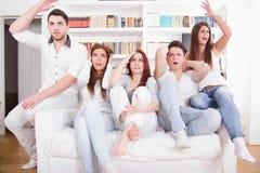 Gruppo di amici che guardano cattivo gioco sulla TV con l'espressione Fotografia Stock