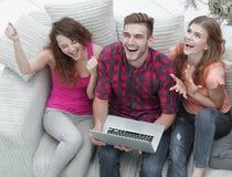 Gruppo di amici che guardano un video su un computer portatile e su una risata Fotografia Stock
