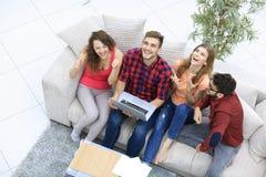 Gruppo di amici che guardano un video su un computer portatile e su una risata Immagini Stock Libere da Diritti