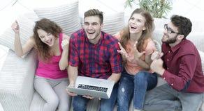 Gruppo di amici che guardano un video su un computer portatile e su una risata Fotografia Stock Libera da Diritti