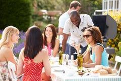 Gruppo di amici che hanno barbecue all'aperto a casa Immagini Stock Libere da Diritti
