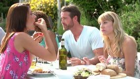 Gruppo di amici che hanno barbecue all'aperto a casa video d archivio