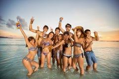 Gruppo di amici che hanno divertimento sulla spiaggia di estate Immagine Stock