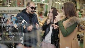 Gruppo di amici che imbrogliano intorno nel supermercato e che provano sui vetri per una festa di Natale festiva stock footage