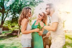 Gruppo di amici che mangiano le birre e che cucinano sul barbecue del giardino Stile di vita, concetto di svago fotografia stock