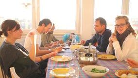 Gruppo di amici che mangiano pranzo a casa video d archivio
