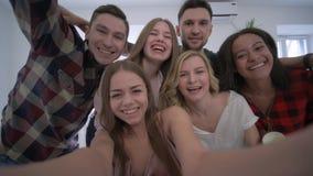 Gruppo di amici che posano insieme per il selfie sul partito, sullo smartphone della tenuta della ragazza e sulla foto domestici