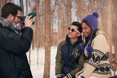 Gruppo di amici che prendono le foto istantanee nella neve nell'inverno fotografia stock