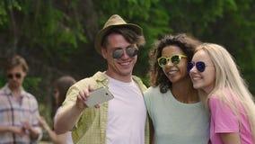 Gruppo di amici che prendono selfie al partito, giovani divertendosi all'aperto video d archivio
