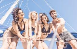 Gruppo di amici che prendono selfie dalla barca Fotografie Stock