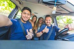 Gruppo di amici che prendono un selfie nell'automobile fotografia stock