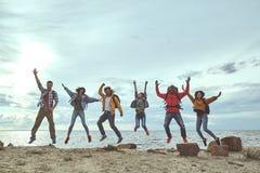 Gruppo di amici che saltano sulla spiaggia fotografia stock