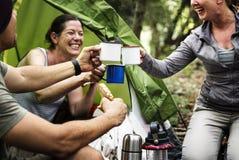 Gruppo di amici che si accampano nella foresta fotografia stock
