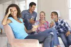 Gruppo di amici che si rilassano insieme su Sofa Drinking Wine At Home Immagine Stock