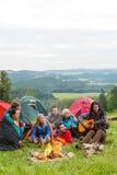 Amici di campeggio che giocano chitarra accanto alla natura del fuoco Immagine Stock