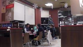 Gruppo di amici che si siedono alla tavola che gode del pasto video d archivio