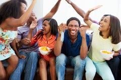Gruppo di amici che si siedono insieme su Sofa Watching TV Immagine Stock
