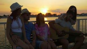 Gruppo di amici che si siedono sul banco e che cantano con una chitarra al tramonto su un pontone stock footage