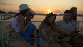 Gruppo di amici che si siedono sul banco e che cantano su un ponte sopra il mare al rallentatore archivi video