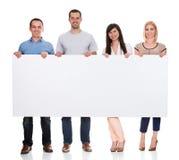 Gruppo di amici che tengono cartello Immagini Stock