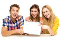 Gruppo di amici che tengono documento in bianco Fotografia Stock