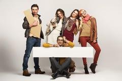 Gruppo di amici che tengono la scheda dell'annuncio Fotografia Stock