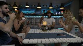Gruppo di amici che tostano le bevande al salotto della barra che celebra i vetri del tintinnio e che si diverte archivi video