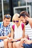 Gruppo di amici che utilizzano smartphone nella città universitaria Fotografia Stock Libera da Diritti