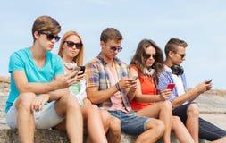 Gruppo di amici con gli smartphones all'aperto Fotografia Stock
