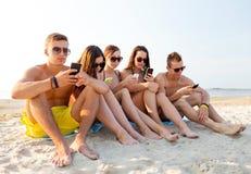 Gruppo di amici con gli smartphones sulla spiaggia Fotografie Stock Libere da Diritti