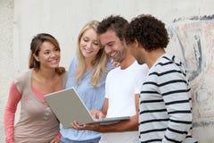 Gruppo di amici con il computer portatile Fotografie Stock Libere da Diritti