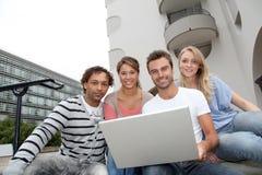 Gruppo di amici con il computer portatile Fotografia Stock