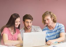 Gruppo di amici con il computer portatile che si siede davanti al fondo rosa dello spazio in bianco Immagine Stock